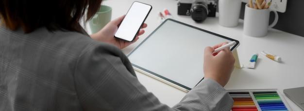 Ritagliata foto della designer femminile che lavora su dispositivi digitali mock-up e forniture di design