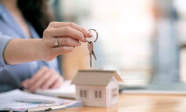 Scatto ritagliato di un'agente immobiliare femminile che tiene le chiavi di casa dando uno spazio per la copia del nuovo proprietario
