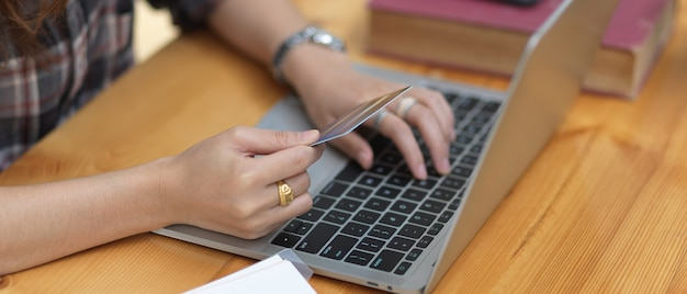 Ritagliata colpo di shopping femminile e pagamento online con carta di credito sul computer portatile