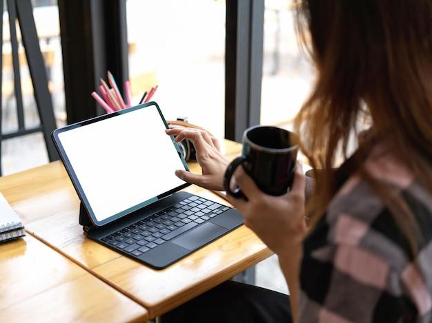 Ritagliata colpo di adolescente femminile che tiene tazza e utilizzando la tavoletta digitale sulla tavola di legno nel percorso di residuo della potatura meccanica del caffè