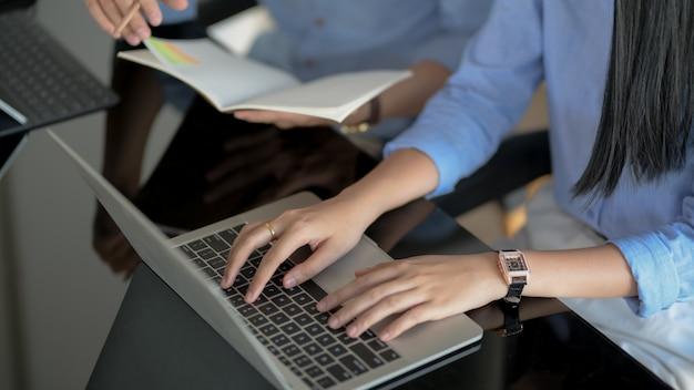 Colpo potato della femmina che digita sul computer portatile mentre il suo briefing del collega sul loro progetto