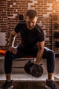 Ritagliata colpo di uomo di forma fisica che fa esercizio di riccioli di concentrazione lavorando con manubri in palestra.