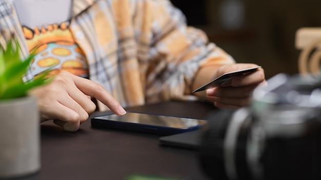Scatto ritagliato di fotografo freelance che utilizza smartphone e tiene in mano una carta di credito