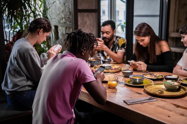 Ritagliata foto di un gruppo di amici che fanno colazione nella cucina comune, ognuno è sul proprio smartphone. concetto di dipendenza gadget