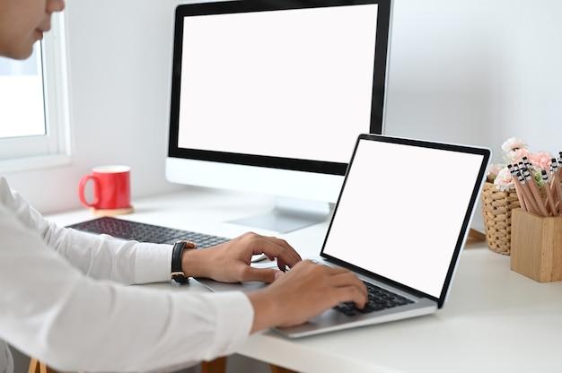Ritagliata colpo di mani che digitano sul laptop con schermo vuoto sullo spazio di lavoro.