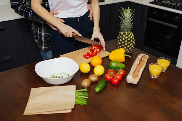 Ritagliata colpo di marito che abbraccia da dietro la moglie mentre prepara l'insalata