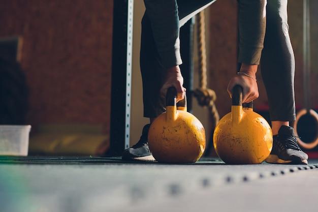 Colpo potato dell'atleta maschio che fa gli esercizi con la campana del bollitore. attrezzature per sollevamento pesi, sollevamento pesi e cross fit. sport, concetto di fitness.
