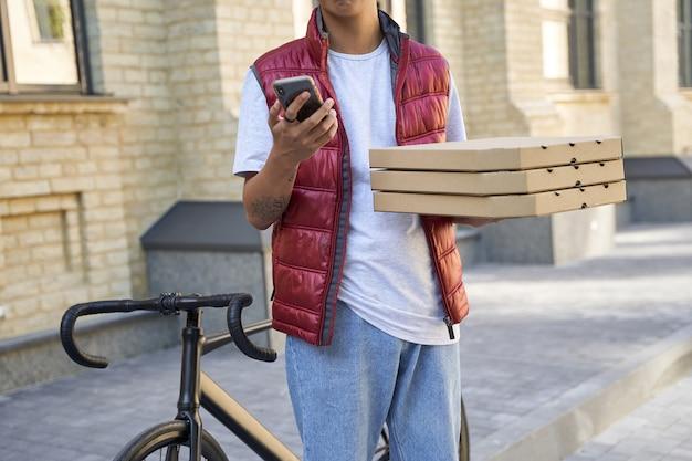 Scatto ritagliato di un corriere maschio che tiene scatole con pizza e usin