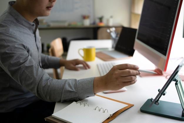 Colpo ritagliato uomo che analizza gli investimenti in borsa sul computer in ufficio.