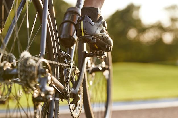 Scatto ritagliato di un uomo che va in bicicletta all'aperto si concentra sulle gambe maschili