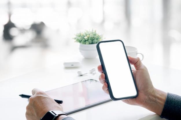 Colpo ritagliato della mano dell'uomo che tiene smartphone e penna a schermo vuoto mentre si lavora in ufficio.