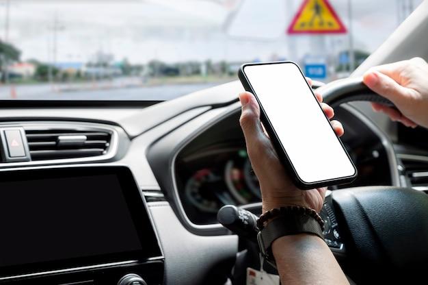 Colpo ritagliato della mano dell'uomo che tiene lo smartphone a schermo vuoto durante la guida.