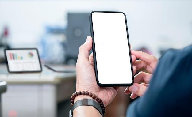 Ritagliata colpo di mano dell'uomo che tiene smartphone schermo vuoto con sfondo sfocato.