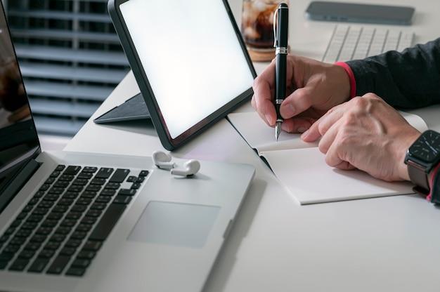 Colpo ritagliato della mano dell'uomo usando la penna che scrive sul taccuino mentre si è seduti al tavolo con il computer in cima.
