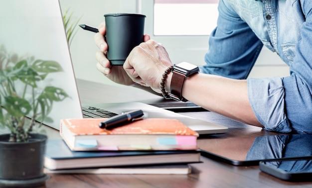 Ritagliata colpo di mano dell'uomo con orologio da polso digitale e tenendo la tazza di caffè, guardando l'orologio da polso e fare una pausa durante il lavoro.