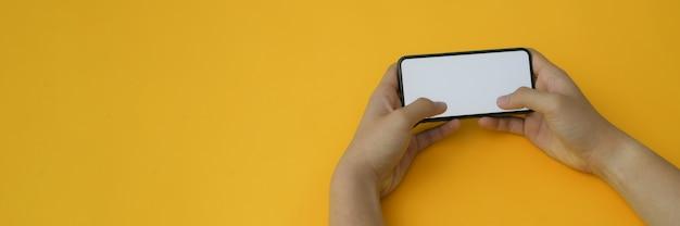 Colpo potato di un uomo che tiene lo smartphone orizzontale dello schermo in bianco