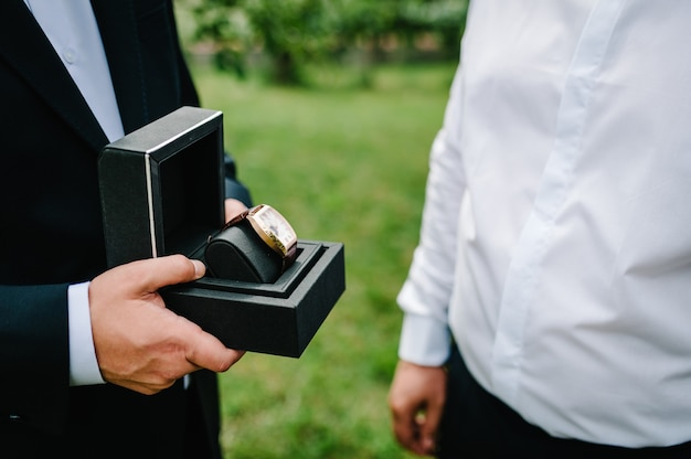 Inquadratura ritagliata di un uomo che indossa un abito elegante e tiene l'orologio da polso. man mano con elegante orologio di lusso costoso con cinturino in pelle su uno sfondo di natura.