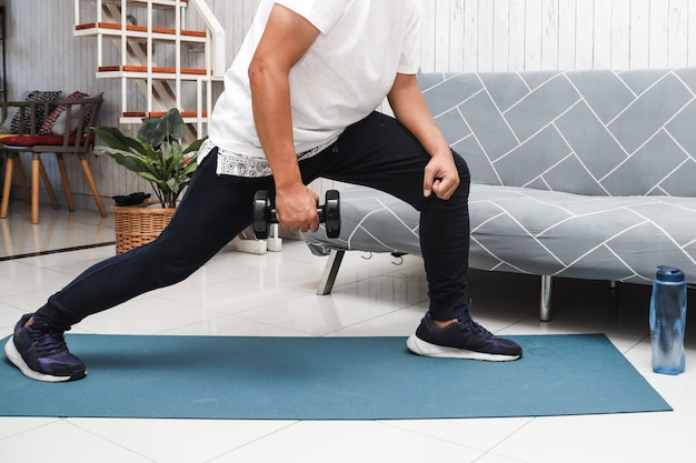 Scatto ritagliato di un uomo in camicia bianca su un tappetino blu che solleva pesi con mini manubri a casa