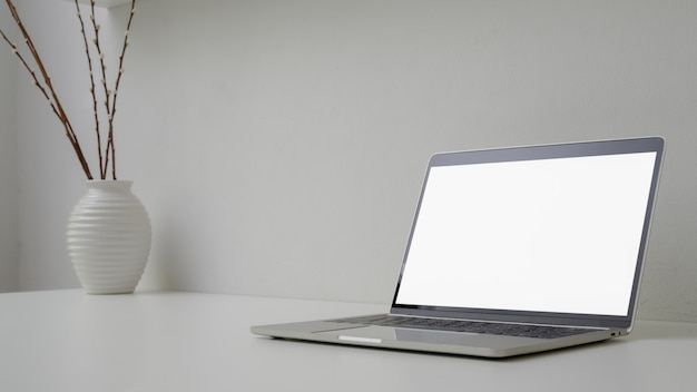 Colpo potato di area di lavoro minima con lo spazio aperto del computer portatile, del vaso e della copia dello schermo in bianco