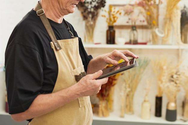 Scatto ritagliato di un uomo anziano moderno che fa l'inventario delle scorte mentre lavora nello spazio della copia del negozio di fioristi