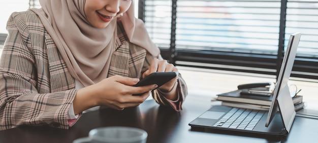 Ritagliata colpo di donna d'affari musulmana in hijab marrone e abbigliamento casual seduto e utilizzando smartphone.