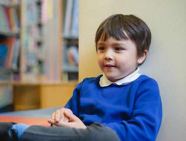 Ritagliata colpo di bambino in età prescolare seduto sul divano godersi il tempo felice in biblioteca a scuola