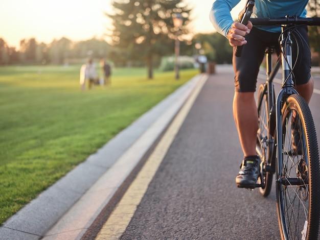 Scatto ritagliato di un ciclista professionista che indossa un allenamento sportivo sulla strada del parco