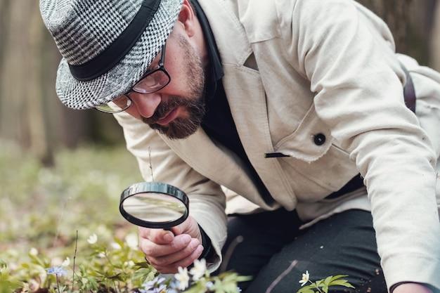 Ritagliata colpo di uomo dall'aspetto raffinato che studia fiore attraverso la lente d'ingrandimento inginocchiato a terra all'aperto