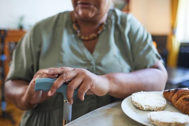 Colpo ritagliato di una donna afroamericana anziana che tiene in mano una casa di cura di canna e una copia di sfondo della mobilità ...