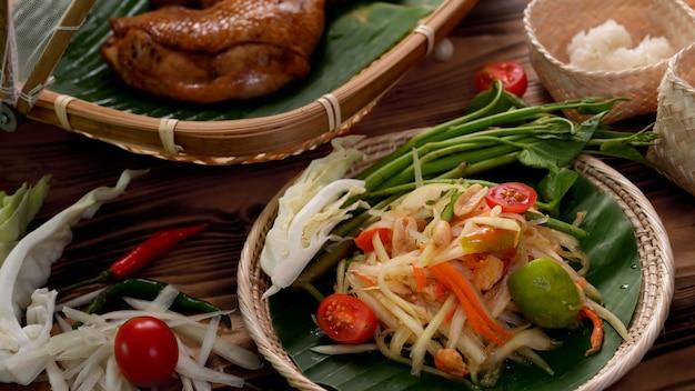 Colpo potato di somtum, alimento tradizionale tailandese con pollo grigliato e riso appiccicoso sul lavoro in vimini