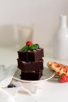 Colpo potato dei brownie del cioccolato della pila sul piatto bianco con la foglia di menta e la fragola sulla cima