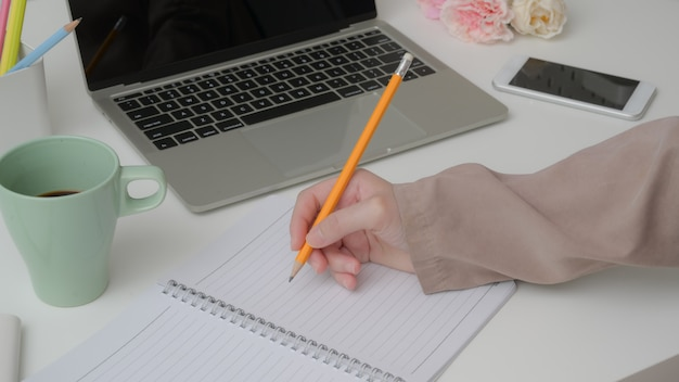 Il colpo potato dello studente universitario prende la breve nota sul taccuino mentre legge il testo