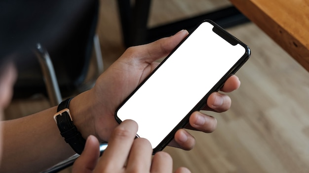 Vista del colpo ritagliata delle mani dell'uomo che tiene il telefono astuto con lo schermo in bianco dello spazio della copia per il messaggio di testo o il contenuto informativo femminile che legge il messaggio di testo sul telefono cellulare durante l'ambiente urbano.