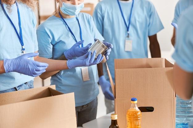 Colpo ritagliato di volontari in maschere protettive uniformi blu e guanti che smistano cibo in scatola per l'imballaggio