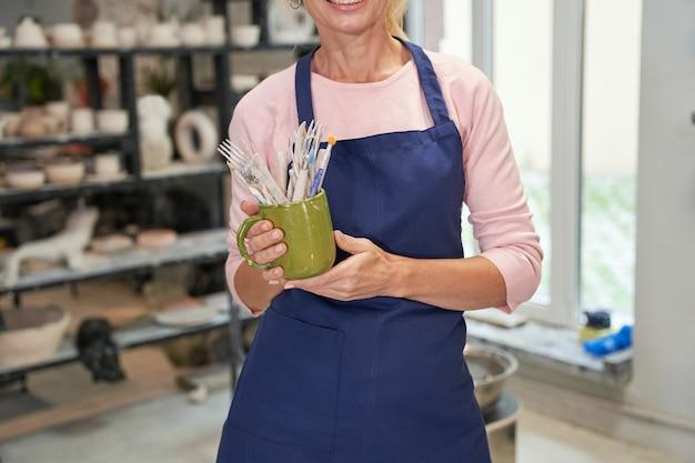Colpo ritagliato di donna in grembiule blu che tiene pennelli per strumenti per creare ceramiche di argilla fatte a mano