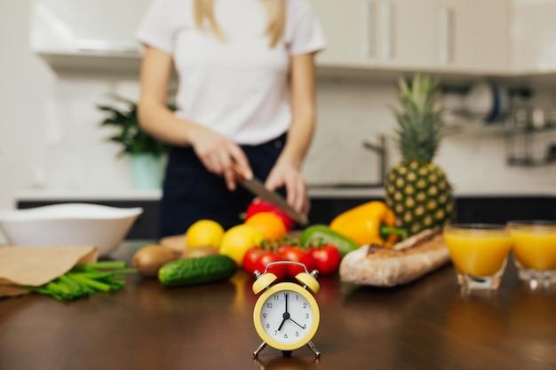 Ritagliata colpo di donna che cucina insalata di verdure per cena focus sul piccolo orologio giallo sul tavolo