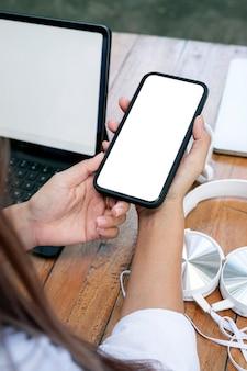 Ritagliata colpo della mano della donna che tiene smartphone schermo vuoto.