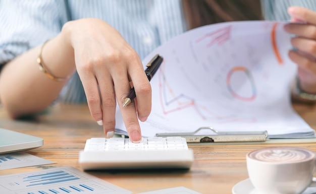 Ritagliata colpo della mano della donna usando la calcolatrice mentre si è seduti al tavolo in ufficio a casa.