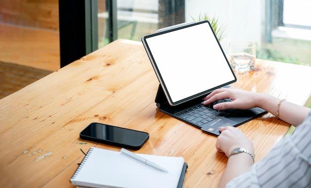 Ritagliata colpo di mano della donna con carta di credito e lavorando sul computer tablet mentre si è seduti al tavolo.