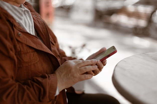 Scatto ritagliato di una donna che usa il cellulare, legge i messaggi sul cellulare in un bar della città