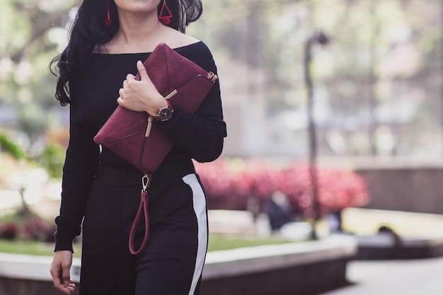 Ritagliata colpo di donna che cammina indossando abiti casual e che tiene una borsa