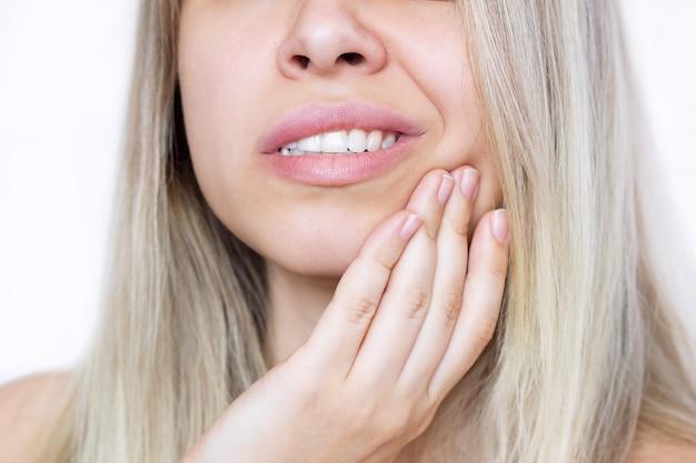 Ritagliata colpo di una giovane bella donna bionda con un mal di denti che tiene la sua guancia isolata .. la ragazza soffre di mal di denti