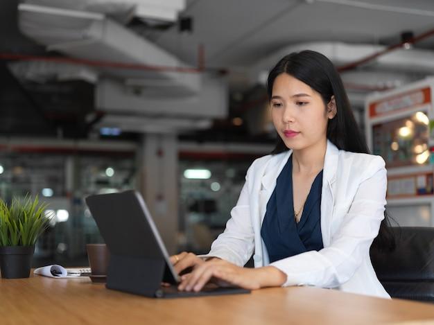 Ritagliata colpo di giovane bella donna di affari che digita sulla tastiera del tablet mentre si lavora nella stanza dell'ufficio
