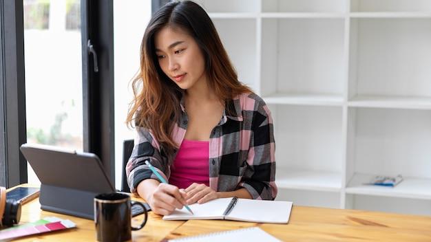 Ritagliata colpo di giovane donna libero professionista che lavora con tavoletta digitale e cancelleria sulla tavola di legno in libreria