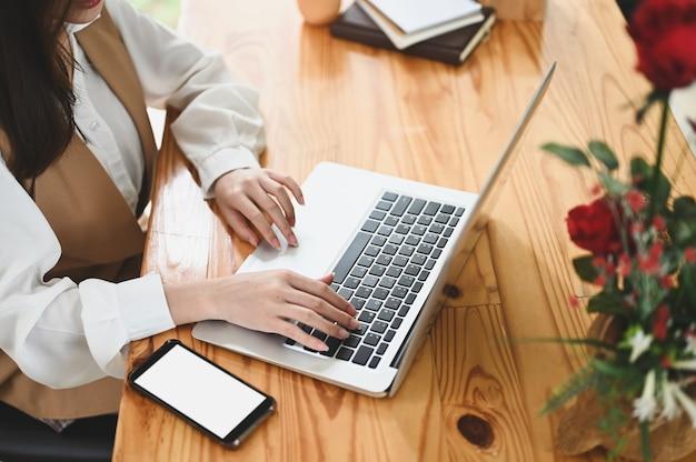 Ritagliata colpo di giovane donna che lavora al suo progetto con mock up computer portatile in ufficio moderno.
