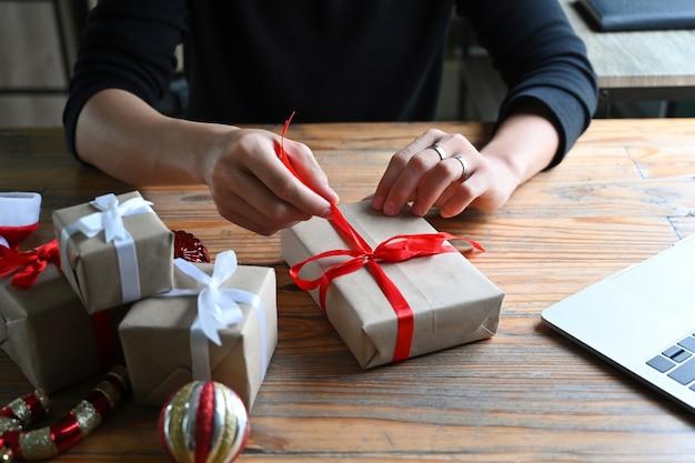 Ritagliata colpo giovane che decora i regali di natale.