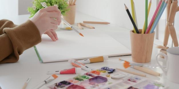 Colpo potato di giovane progettista femminile professionista che sceglie il colore per il suo progetto mentre scrivendo sul computer portatile