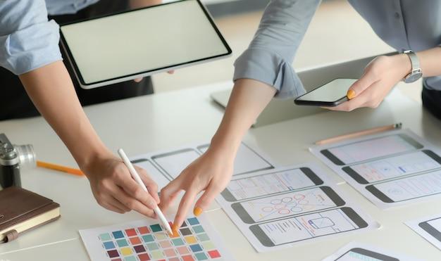 Colpo potato di giovane gruppo del progettista di ux che lavora al progetto di applicazione dello smartphone con l'utilizzo della compressa digitale nella stanza moderna dell'ufficio.