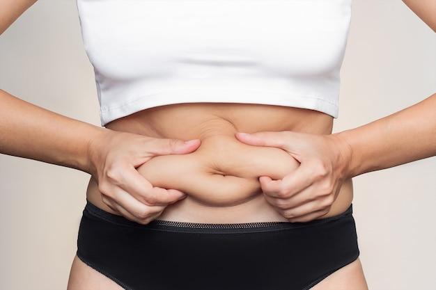 Un'inquadratura ritagliata di una giovane donna che si tiene per il grasso sullo stomaco che mangia troppo peso in eccesso