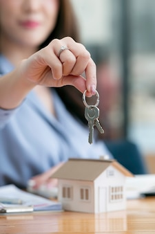 Il colpo ritagliato della giovane donna sta mostrando una chiave di casa sua. concetto di bene immobile.